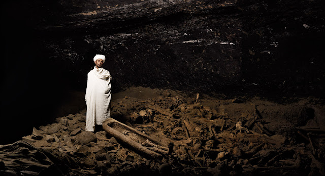 "YEMREHANNA KRISTOS  Keas Hable Mariyam, the monk of the cavern church, poses on top of an estimated 5740 remaining pilgrim corpses. ""Most of them came from Jerusalem and now they remain here to rest."" Lalibela, Ethiopia"