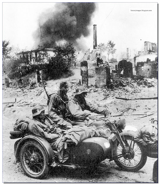 Liebstandarte soldiers ride  motor-cycle through  destroyed Russian village
