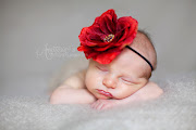 5 days old newborn baby girl with beautiful red flower