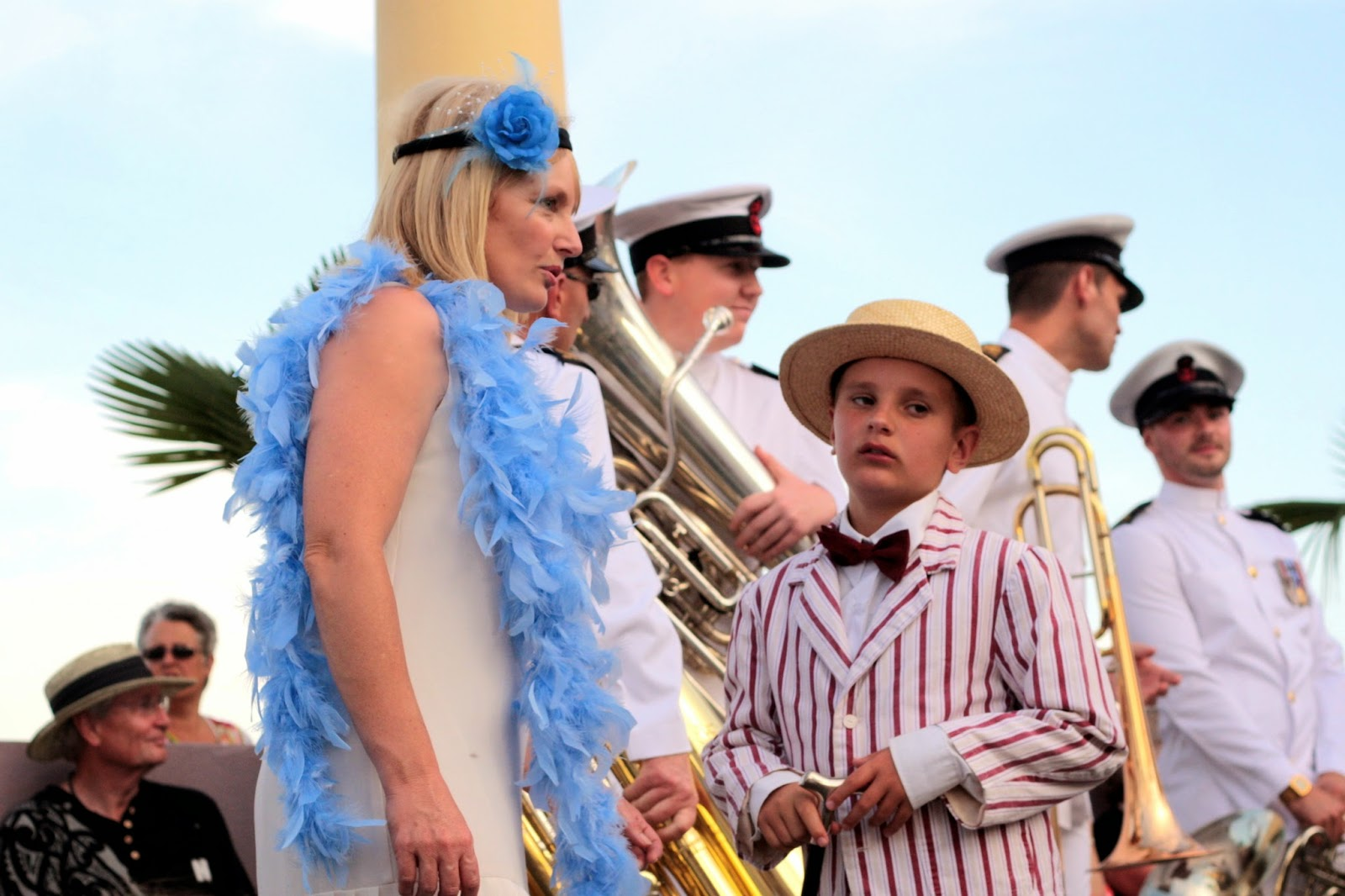 A woman wears a blue feather boa. Her son wears a stripped blazer, a straw boater, and a petulant look.