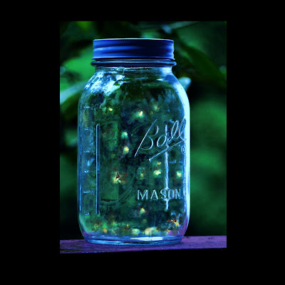 a glass jar with lid with lots of fire flies inside lighting up