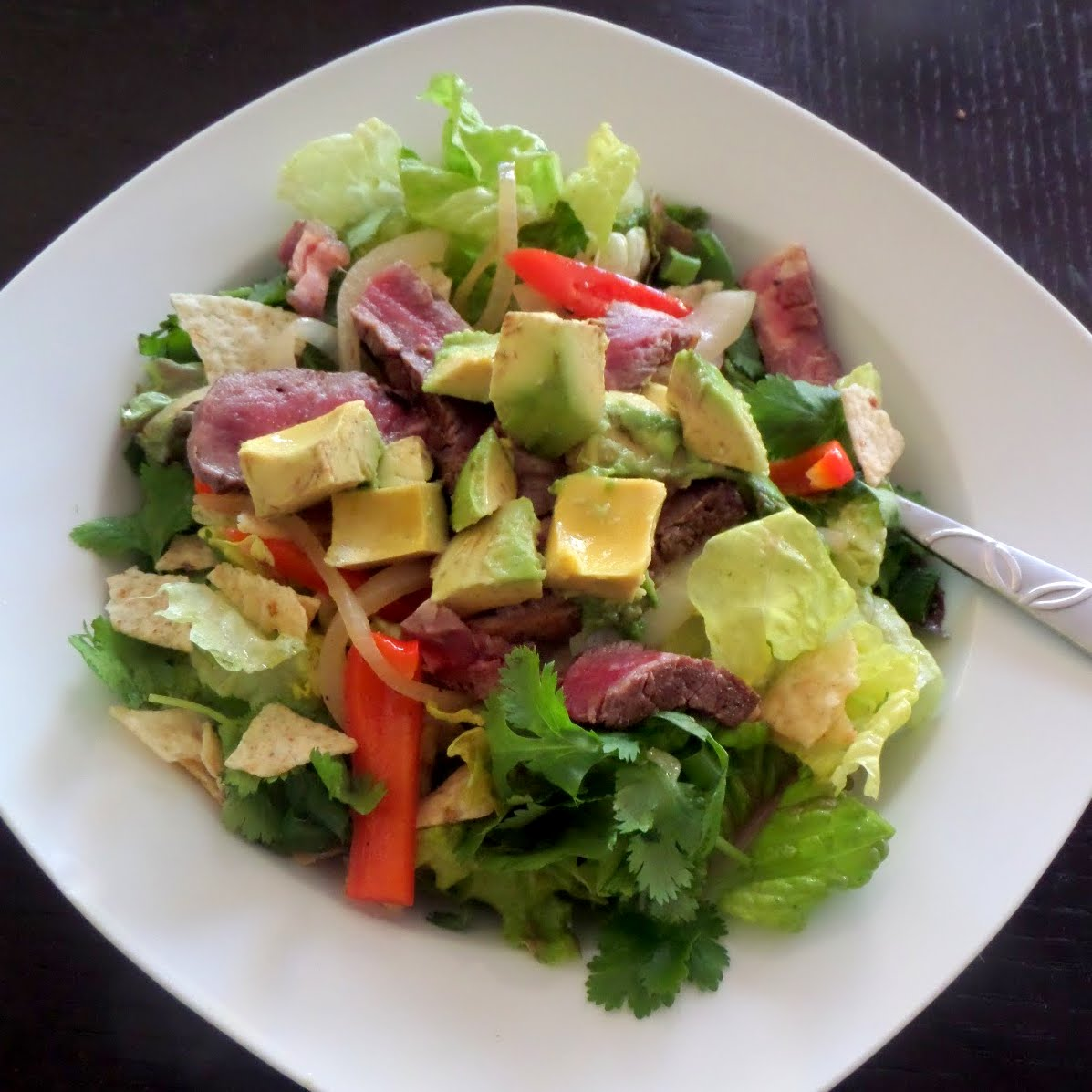 Steak Fajita Salad:  A green salad topped with sauteed pepper, onion, and leftover steak slices.  Also, avocado, cilantro, and crushed tortilla chips.