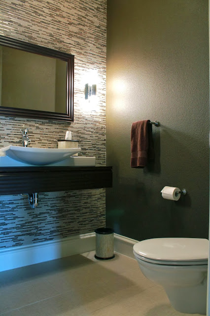 stunning transitions between mosaic tiles and soft patterned wall paper in the corner of the bathroom