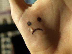 Crying emoticon on the hand