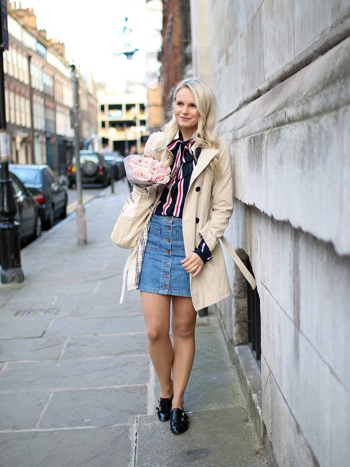 a women stands in a quaint london street, wearing a bow neck stripe top and denim skirt with neutral colour trench coat
