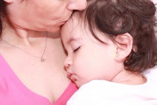 Bebé dormido en brazos de mamá