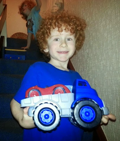 6 year old with Green Toys race car and flatbed truck