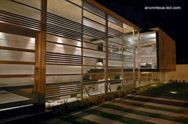 Vista nocturna de la fachada transiluminada de la vivienda