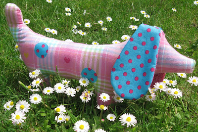 Simple handmade fabric dog in dotty fabrics photographed on grass