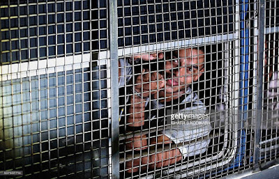 Former president Mahinda Rajapakse's second son Yoshitha Rajapakse is taken in handcuffs after being remanded in custody for two weeks in Kaduwela. Rajapakse was arrested along with four others in connection with money laundering when his father was president. (AFP/Ishara S. KODIKARA)