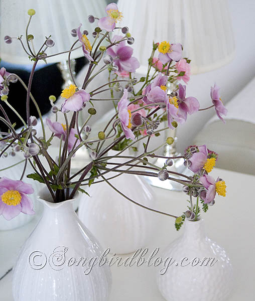 pink and yellow garden flowers in white vases