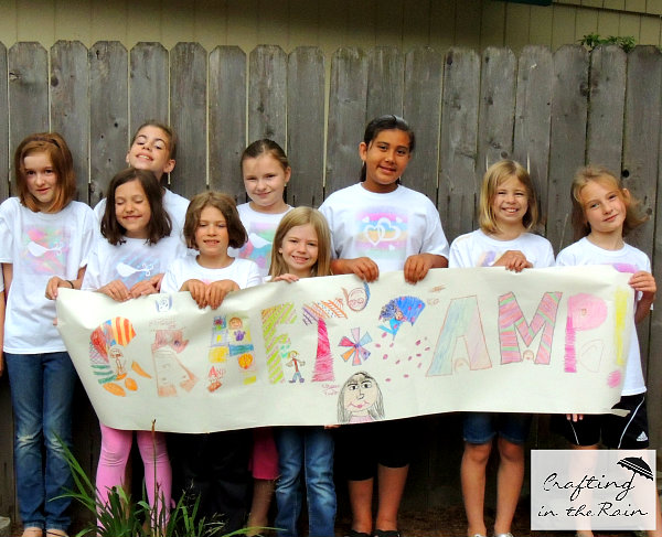girls holding craft camp sign
