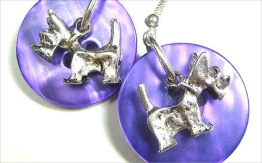Drop dangle earrings have silver dog charms layered over shiny purple buttons