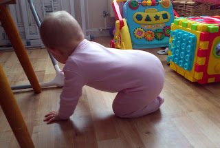 baby in pink onesie crawling under high chair