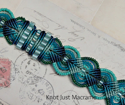close up of knotted micro macrame bracelet in shades of teal and turquoise