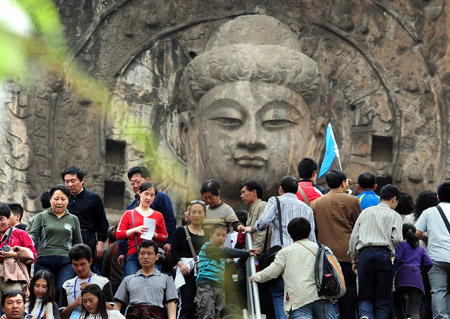 Buddha statue crowded by visitors in the Longmeng Grottoes in Luoyang City, China