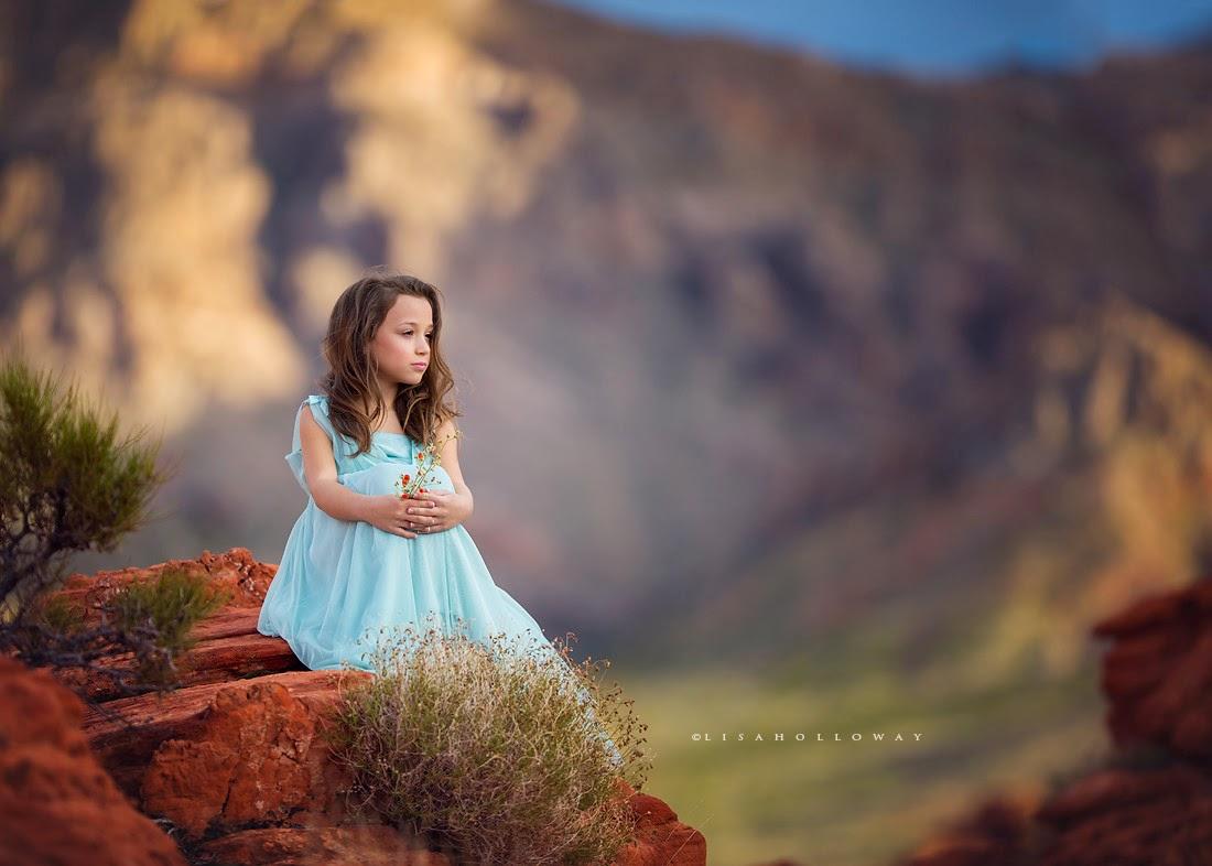 photo de Lisa Holloway représentant une jeune fille en robe bleu pale assise sur un rocher