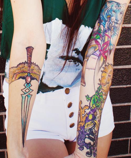 Tatuagem feminina no braço adaga e colorida