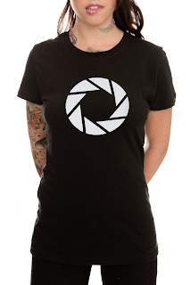 This is a sexy girl with tatoos wearing an Aperture logo T-shirt
