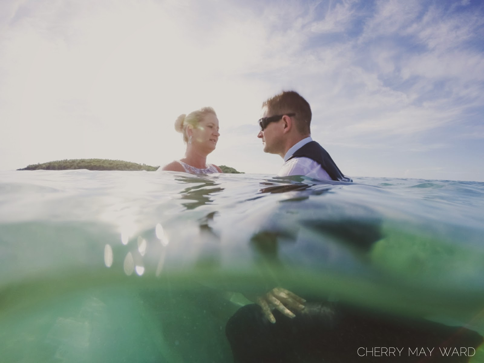 bride and groom photos half underwater, photograph of wedding couple half underwater, trash the dress, underwater photos of wedding dress, Koh Samui wedding underwater
