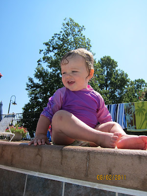 baby in a rashguard swim suit by the side of a swimming pool, not a bikini