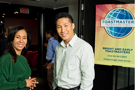 two toastmasters members stand together outside of an event