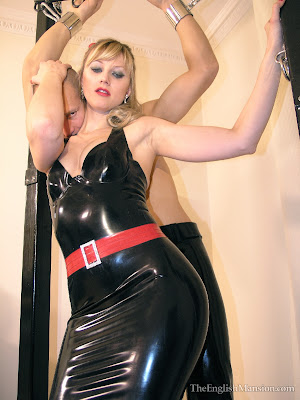 Sexy Blonde Rubber clad mistress in black latex dress