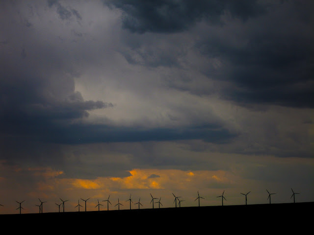A long line of windmills on the horizon under stormy skies on I-80 in Wyoming.