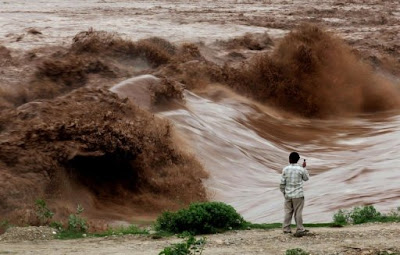 An Indian villager watching fast moving water during a flash flood of the Tawi river
