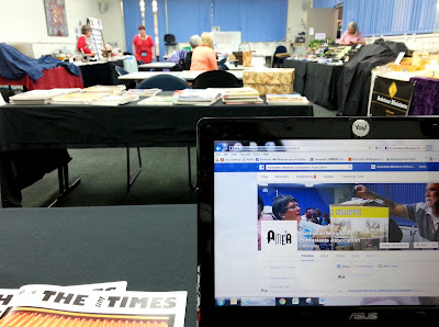 View of a doll's house show sales room from behind a laptop at one of the tables.