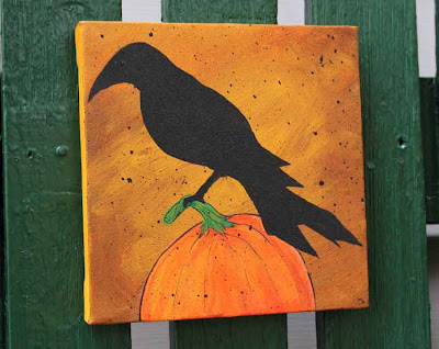 acrylic painting of a crow perched on a pumpkin