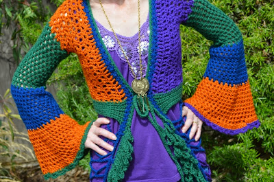 Crocheted mesh duster coat in blue, orange, green and purple with bell sleeves and loopy fringe along the edges.