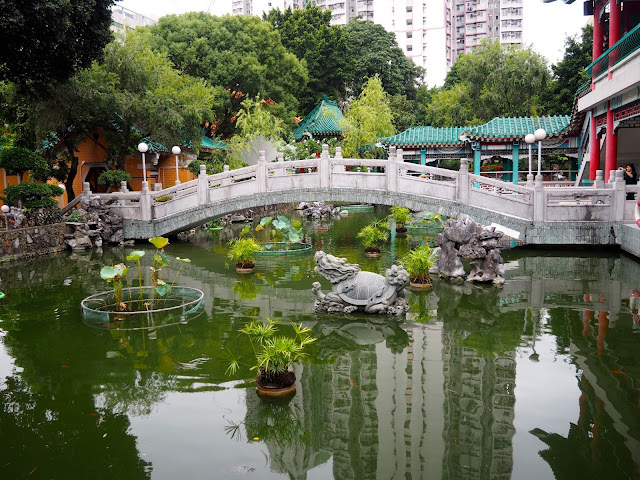 Bridge and statues on the pond in the garden of Sik Sik Yuen Wong Tai Sin Temple, Hong Kong