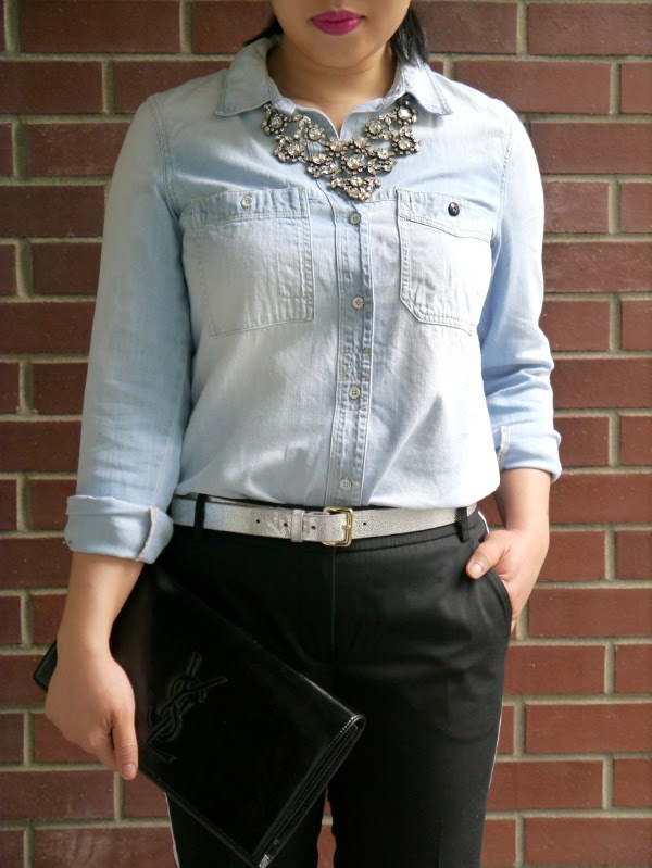 Rhinestone statement necklace, chambray shirt, fuchsia lipstick, Saint Laurent Belle de Jour clutch, silver leather belt, tuxedo trousers