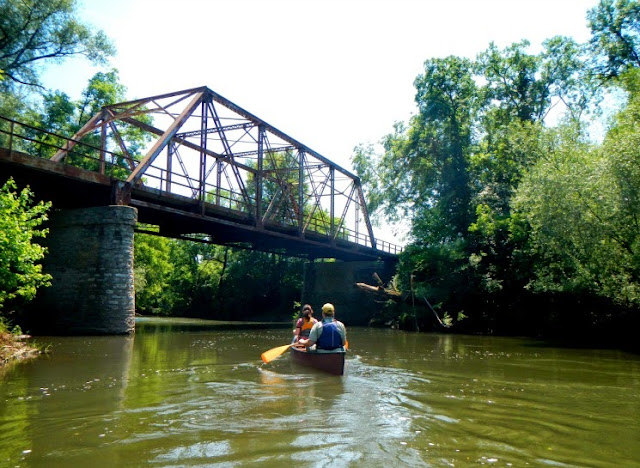 canoeing under the train tracks along the root river state trail