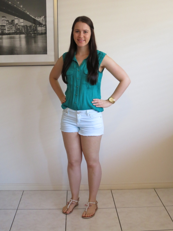 A monochrome green outfit with mint green shorts, jewel green top, gold watch and sandals.