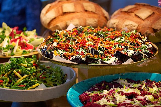 Photo of large platters of lunch vegetable entrees with loaves of bread in the background at Nopi in London, England.