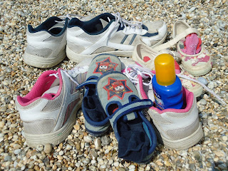 The whole families shoes on the shingle beach at Durdle Door
