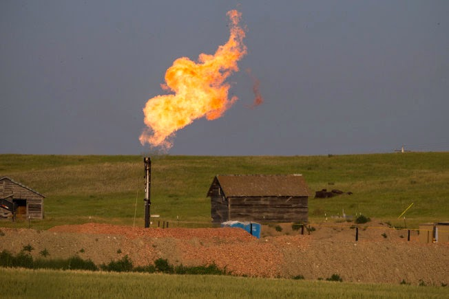 A gas flare burns near an abandoned building in July 2013 outside Williston, N.D. (Credit: www.usnews.com) Click to Enlarge.