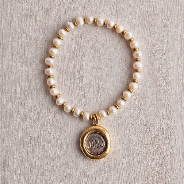 http://www.whitetrufflestudio.com/collections/bracelets/products/monogram-seal-charm-pearl-bracelet