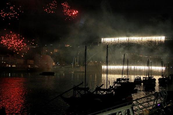 Cascata de luz caindo da Ponte de Dom Luís. Barcos rabelos em promeiro plano, em contra-luz