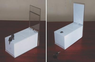 biała urna z plexi zamykana na kluczyk z miejscem na cenę lub opis