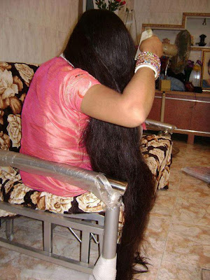 Homely college girl from Tamil Nadu combing out her hair sitting in a sofa.