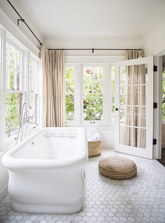 Bathroom spacious enough to accommodate a freestanding bathtub in a separate room filled with large openingsImage by Brittany Ambridge via Domino