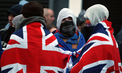 Protesters with covered faces object to the removal of the Union flag from Belfast City Hall