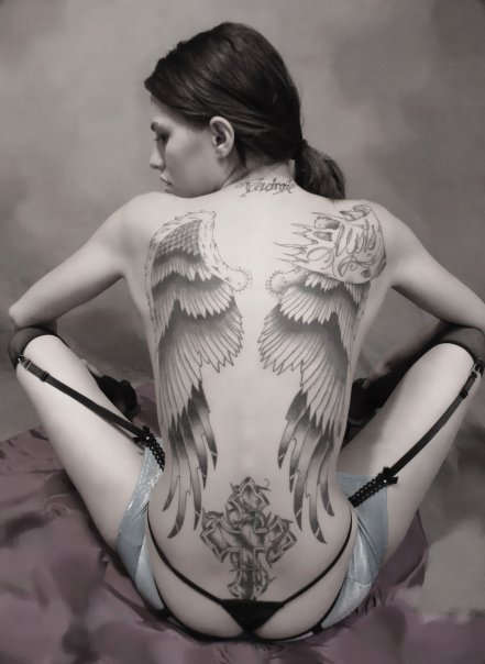 big wings tattoo on the back and a cross tattoo on the waist