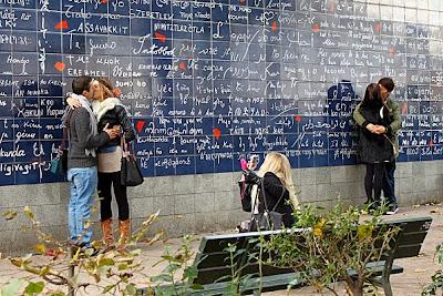 deux couples d'amoureux devant le mur des je t'aime