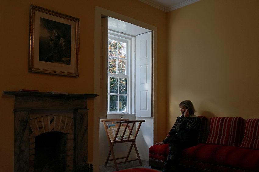 Pormenor duma sala, com lareira do lado esquerdo da janela e uma mulher à direita a ouvir no audiofone