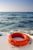Image of a Life buoy on the back of a boat in the water: Water Safety means respect for the water
