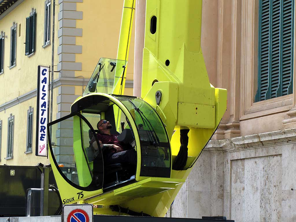 Maneuvering the boom lift of a huge cherry picker, Livorno